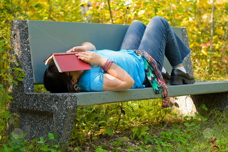 Tired Girl stock photo, A nine year old girl lying on a park bench, with a book over her face by Richard Nelson