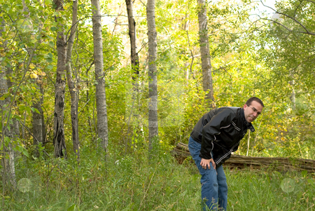 Man With Poison Ivy stock photo, A man coming out of the bush scratching himself because he is itchy by Richard Nelson