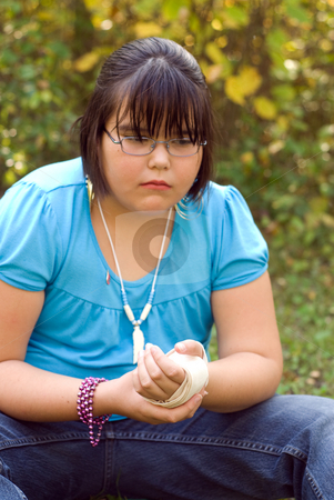 Injured Wrist stock photo, A nine year old girl holding her injured wrist and being brave with the pain by Richard Nelson