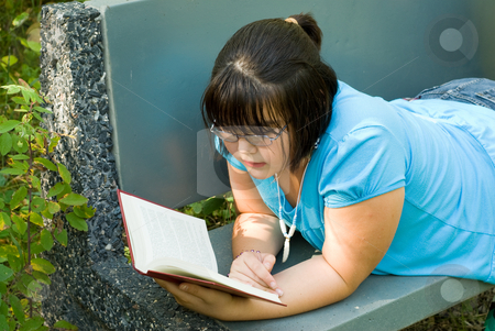 Relaxation stock photo, A young girl lying on a park bench, reading a novel by Richard Nelson