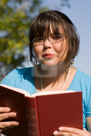 Girl Reading A Novel stock photo, A young girl sitting outside, reading a novel by Richard Nelson