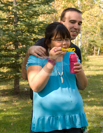Playing stock photo, A nine year old girl and her dad, blowing bubbles outside by Richard Nelson