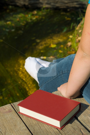 Relaxing Outside stock photo, Someone sitting on a wood dock with their feet over the edge by Richard Nelson