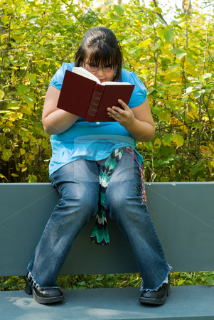 Novel stock photo, A young girl reading a book outside by Richard Nelson
