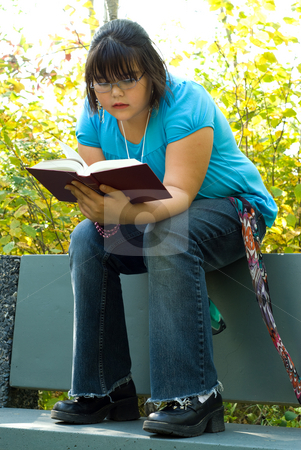 I Love To Read stock photo, A nine year old girl sitting on a park bench, reading a good book by Richard Nelson