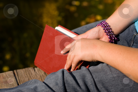 Quiet Time stock photo, Closeup of a book and a girls leg, symbolizing quiet and relaxation by Richard Nelson