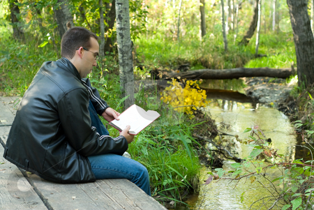 Reading In Peace stock photo, A young man sitting on a bridge reading in peace by Richard Nelson