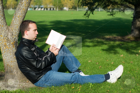 Man Studying Outside stock photo, A caucasian man studying a book outside while leaning against a tree by Richard Nelson