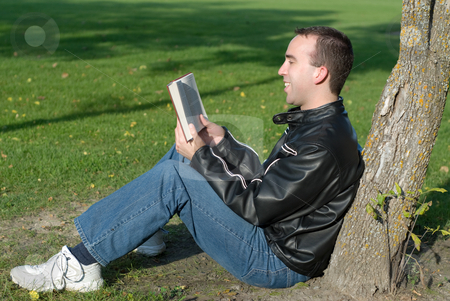Funny Book stock photo, A man reading a humorous book outside by Richard Nelson