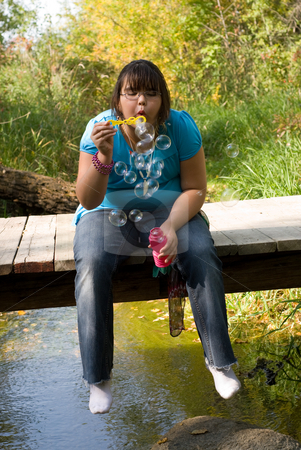 Down By The Creek stock photo, A nine year old girl blowing bubbles by the creek by Richard Nelson