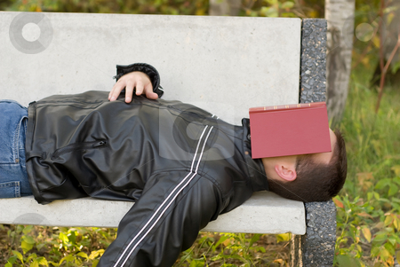 Man Asleep Outside stock photo, A man asleep outside with a book over his eyes by Richard Nelson