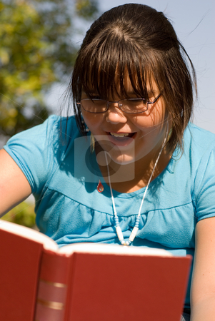 Exciting Book stock photo, A young girl showing excitement at reading her book by Richard Nelson