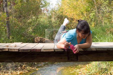 Girl on Bridge stock photo, A girl making a gross face while looking for bugs by Richard Nelson