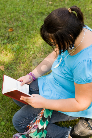 Child Reading A Novel stock photo, A young girl reading a novel outside by Richard Nelson