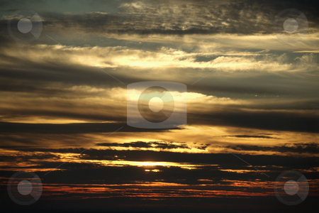 Sunset through clouds. stock photo, Sunset through cloudy sky. by Iofoto Images
