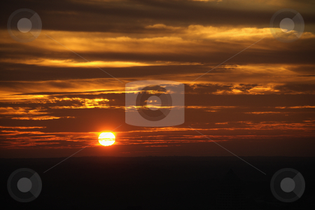 Sunset. stock photo, Sun setting in orange sky with clouds. by Iofoto Images