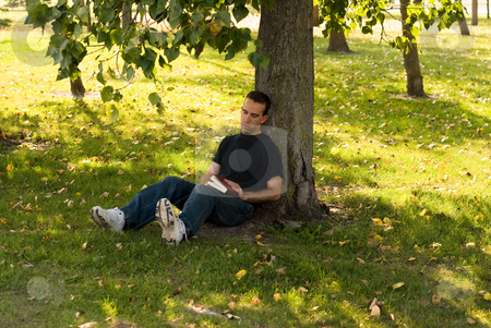 Man Resting Outside stock photo, A young man resting under a shady tree by Richard Nelson
