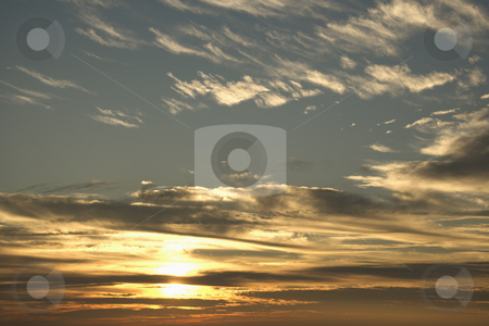 Sunset sky with clouds stock photo, Sun in blue sky with clouds. by Iofoto Images