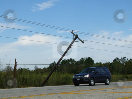 Electrical  stock photo, Electrical and telephone poles were uprooted, leaning, broken, and down.  Poles are dangerously leaning over roadway. by Marburg