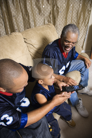 Family watching sports. stock photo, Three male generations of an African-American family watching football game on tv with boy holding remote. by Iofoto Images
