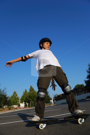 Balancing the Skateboard stock photo, Boy balancing the skateboard shown against the blue sky by Denis Radovanovic