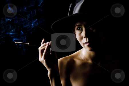 Woman in shadow wearing a black hat with cigarette stock photo, Mysterious woman in shadows with a cigarette by Scott Griessel