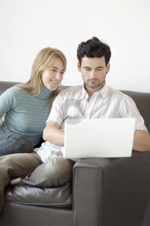 Couple relaxing at home with a laptop computer stock photo, A young couple relaxing at home on the sofa with a laptop computer by Lee Torrens