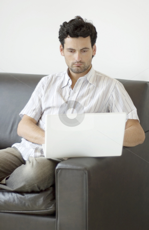 Working from Home stock photo, A young professional man working from home, relaxed on the sofa. by Lee Torrens