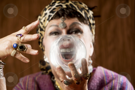 Gyspy with a crystal ball stock photo, Female gypsy fortune teller holding a crystal ball to her eye by Scott Griessel