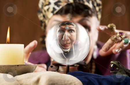 Gyspy seen in a crystal ball stock photo, Female gypsy fortune teller looking into a crystal ball by Scott Griessel