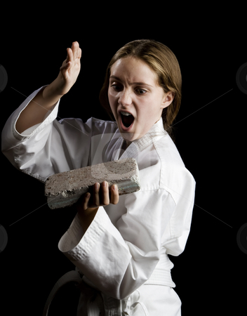 Young girl karate chopping a brick stock photo, Young girl karate chopping a brick on black background by Scott Griessel