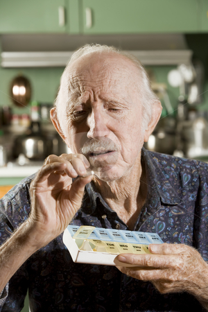 Elder Man with a Pill Case stock photo, Portrait of Elder Man Discussing Medications by Scott Griessel