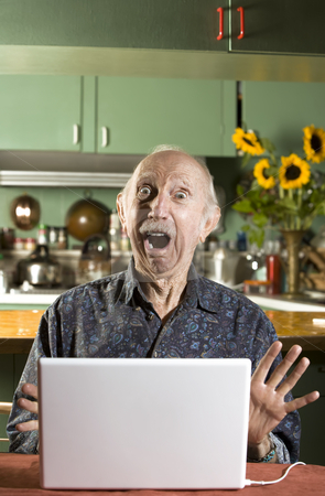 Shocked Senior Man with a Laptop Computer stock photo, Shocked Senior Man in Dining Room with a Laptop Computer by Scott Griessel