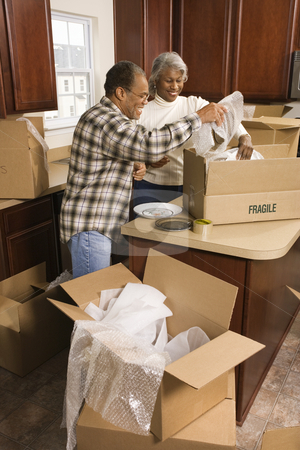 Couple moving. stock photo, Middle-aged African-American couple packing moving boxes in kitchen. by Iofoto Images