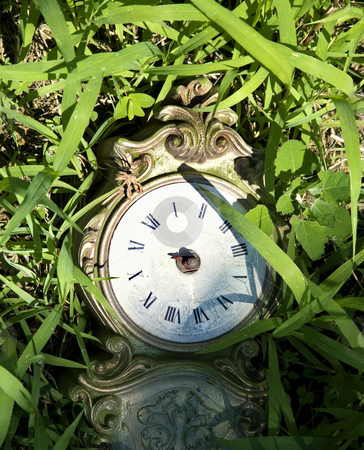 Old broken clock in grass. stock photo, Broken clock lying in grass. by Iofoto Images