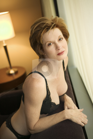 Woman in lingerie. stock photo, Pretty Caucasian woman in lingerie kneeling by window looking at viewer. by Iofoto Images