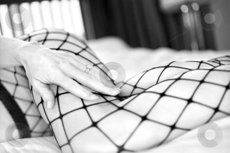 Sexy woman. stock photo, Close up of Caucasian woman in fishnet stockings on bed. by Iofoto Images