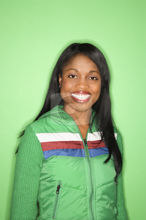 Pretty girl smiling. stock photo, African-American mid-adult woman in green coat on green background. by Iofoto Images