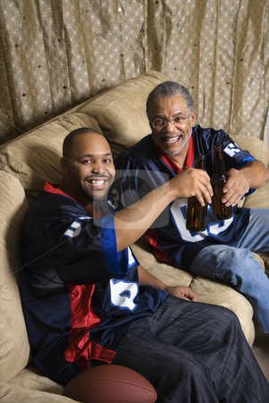 Dad and adult son. stock photo, Portrait of an African-American father and son toasting with beer on couch. by Iofoto Images