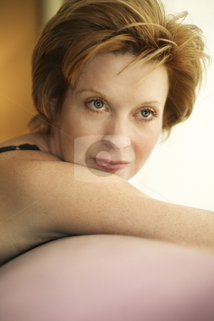 Portrait of woman. stock photo, Portrait of pretty Caucasian woman draped over sofa by window. by Iofoto Images