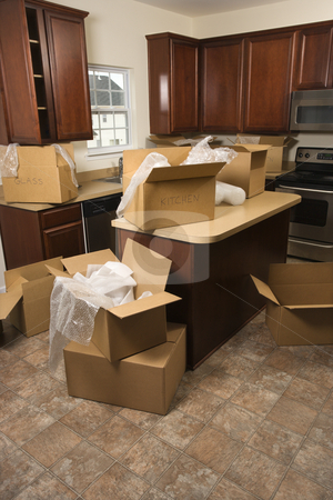 Moving boxes in kitchen. stock photo, Cardboard moving boxes with bubble wrap in kitchen. by Iofoto Images