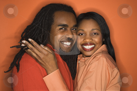 Happy couple portrait. stock photo, Smiling African-American mid-adult couple wearing orange clothing on orange background. by Iofoto Images