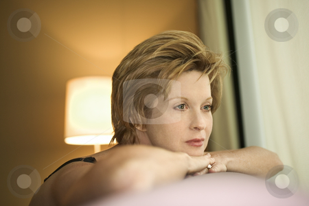 Portrait of woman. stock photo, Portrait of pretty Caucasian woman draped over sofa by window looking out. by Iofoto Images