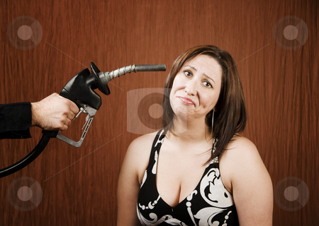 Woman with Gas Nozzle to her Head stock photo, Woman with a gas nozzle pointed like a gun to her head by Scott Griessel