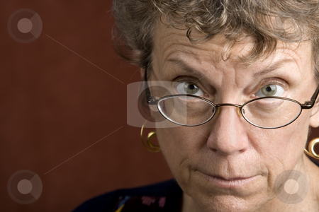 Woman looking over her glasses stock photo, Senior woman looking over the top of her glasses by Scott Griessel