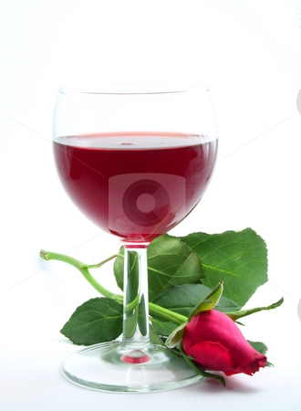 Wine glass stock photo, Wine glass with a rose beside and red wine, on a table, with white bagground by Steen Bartholin Nielsen
