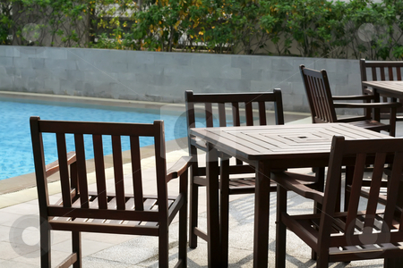 Poolside furniture stock photo, Wooden poolside furniture tables and chairs casual outdoors design by Kheng Guan Toh