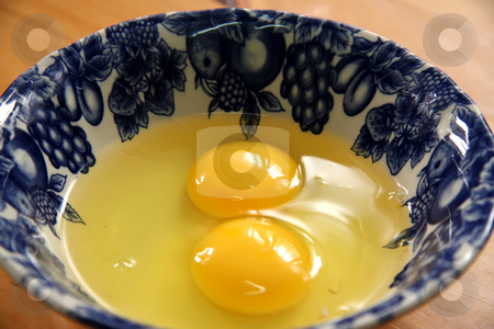 Two raw eggs stock photo, Two raw eggs with yolks liquid in bowl by Kheng Guan Toh