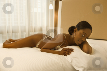 Woman in lingerie. stock photo, Young African American woman lying on bed in lingerie looking at viewer. by Iofoto Images