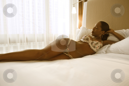 Woman in lingerie. stock photo, Young African American woman lying on bed in lingerie. by Iofoto Images